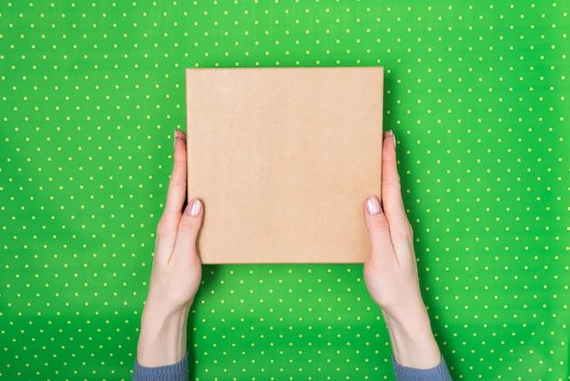 Vierkante kartonnen doos in vrouwelijke handen. bovenaanzicht, groene polka dot