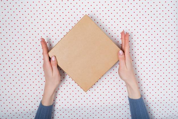 Vierkante kartonnen doos in vrouwelijke handen. bovenaanzicht, witte achtergrond
