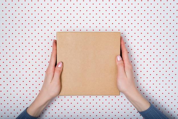 Vierkante kartonnen doos in vrouwelijke handen, bovenaanzicht,