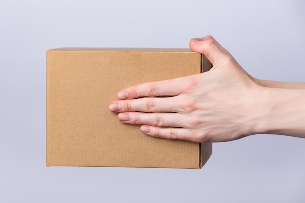 Vierkante kartonnen doos in vrouwelijke handen. levering van pakketten. zijaanzicht. detailopname