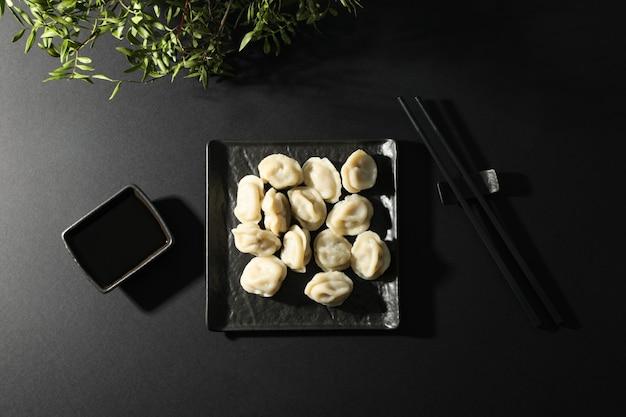 Vierkante plaat met dumplings, stokjes, plant en sojasaus op zwarte achtergrond, bovenaanzicht