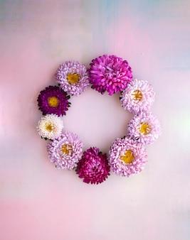Vierkante roze houten banner met asterbloemen die in een kroon liggen. plaats voor tekst.