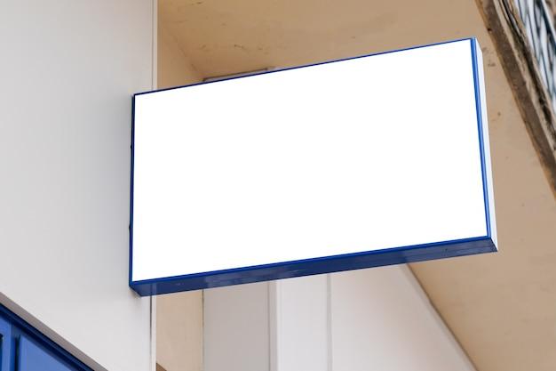 Vierkante signage van het opslaguithangbord op winkelmuur met leeg wit tekenaanplakbord