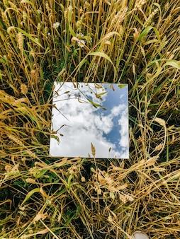 Vierkante spiegel in tarweoren met weerspiegelde blauwe hemel en witte wolken