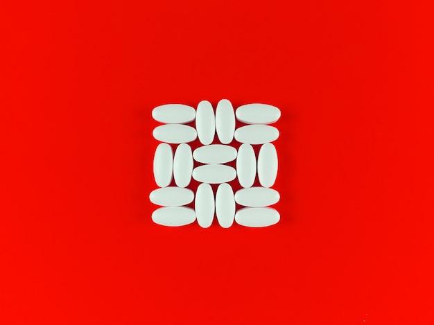 Vierkante vorm gemaakt van witte tabletten op een rode achtergrond.