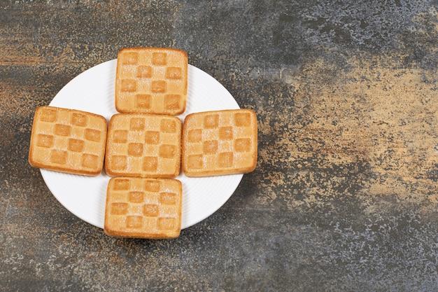 Vierkante zoete crackers op witte plaat.