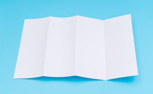 Viervoudig wit sjabloon papier op blauwe achtergrond.