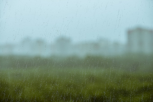 Vies glas met druppels regen. regendruppels op achtergrond van groen, gebouw en hemel in bokeh