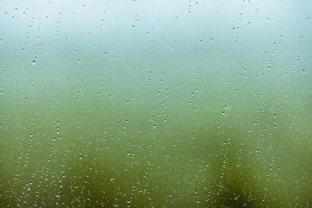 Vies glas met druppels regen. regendruppels op groene en blauwe heldere achtergrond.