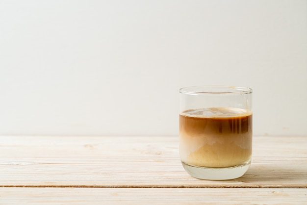 Vies koffieglas, koude melk gegarneerd met hete espresso
