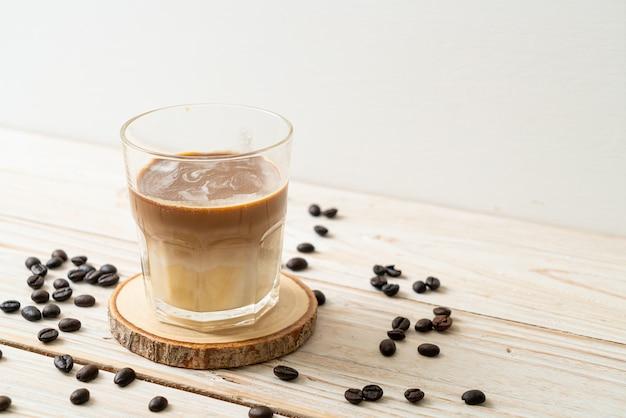 Vies koffieglas, koude melk gegarneerd met hete espressokoffie