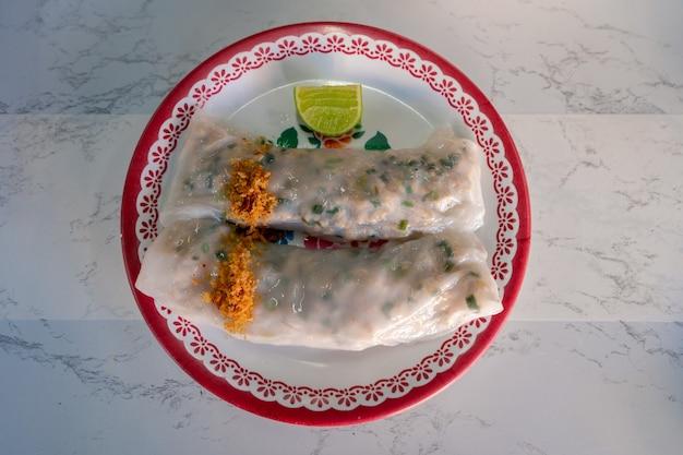 Vietnamees eten gestoomde rijstvellen met gehakt varkensvlees en groenten topping met gebakken knoflook op tafel, fusie van thais vietnamees eten in lokaal straatvoedselontbijt thailand