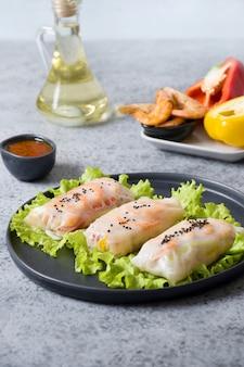 Vietnamees eten loempia's met groenten, garnalen in rijstpapier op grijze stenen achtergrond. detailopname. aziatische keuken. verticaal formaat.