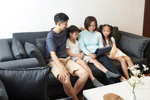 Vietnamees gezin met twee kinderen die op de bank rusten en app gebruiken op de bekwame computer die ze zomervakantie plant