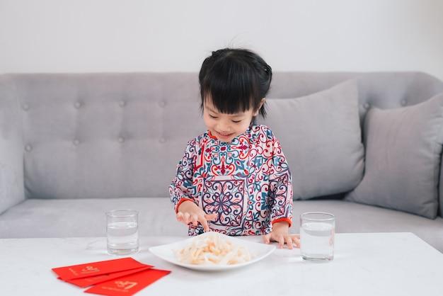 Vietnamees klein meisje in ao dai traditionele kleding, vier thuis nieuwjaar. tet vakantie.