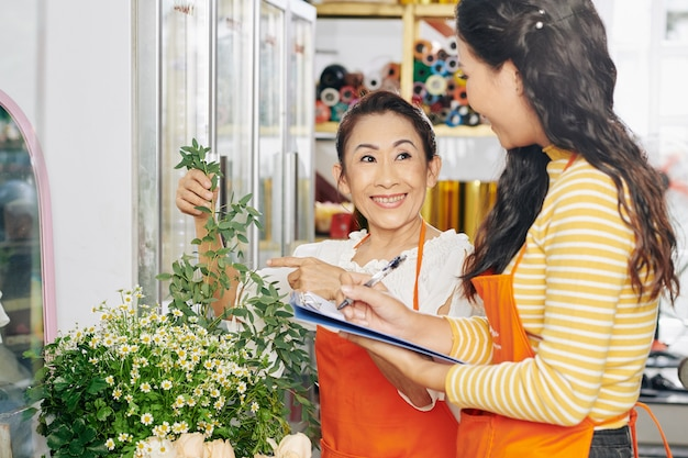 Vietnamese bloemist en haar assistent bespreken hoe ze voor de plant moeten zorgen en maken aantekeningen in het document