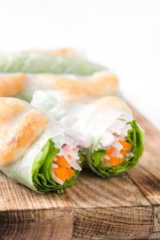 Vietnamese broodjes met groenten, rijstnoedels en garnalen op witte oppervlakte worden geïsoleerd die