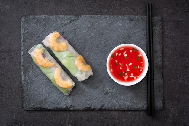 Vietnamese broodjes met groenten, rijstnoedels en garnalen op zwarte lei