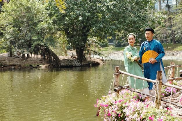 Vietnamese bruid en bruidegom in traditionele ao dai-jurken en hoofddeksels genaamd khan dong die bij de vijver in het stadspark staan