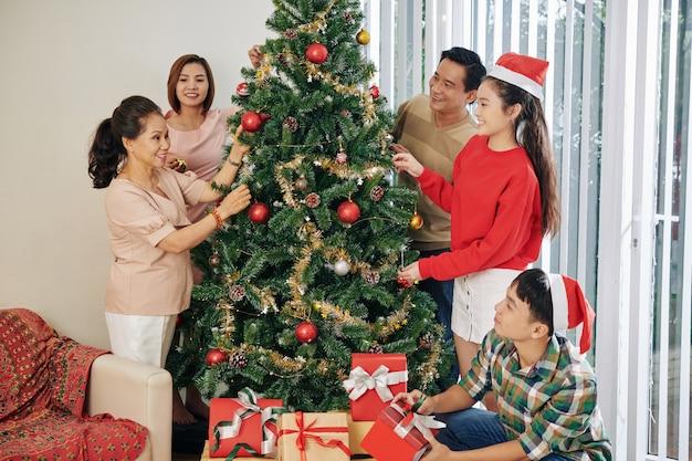 Vietnamese familie die kerstboom verfraait