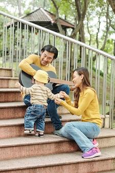 Vietnamese jongeman gitaar spelen en zingen voor zijn dansende zoontje, zijn vrouw zittend op trappen in de buurt