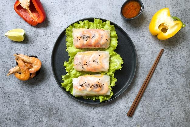 Vietnamese loempia's met garnalen en ingrediënten in rijstpapier op grijze achtergrond. uitzicht van boven. aziatische keuken. horizontale oriëntatie.
