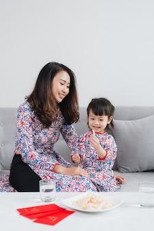 Vietnamese moeder en dochter in ao dai traditionele kleding, vieren thuis het nieuwe jaar. tet vakantie.