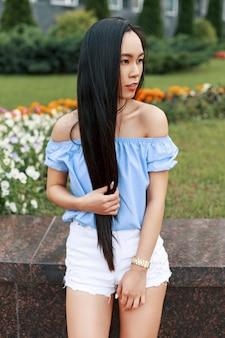 Vietnamese mooie vrouw met lang haar in een blauwe blouse poseren in park in de buurt van bloemen.