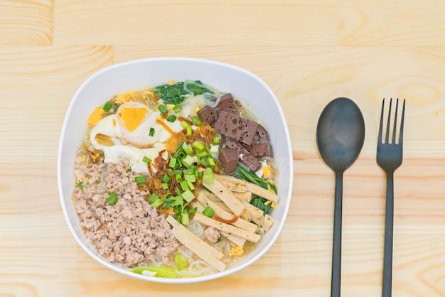 Vietnamese rijstnoedelsoep met varkenskrabbetjes, varkenskorkblokken en gekookt ei.