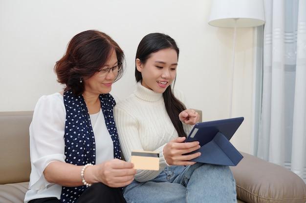 Vietnamese senior vrouw en haar volwassen dochter winkelen samen online terwijl ze op de bank in de woonkamer rusten