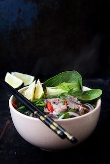 Vietnamese soep pho bo met groenten en rijstnoedels in een kom