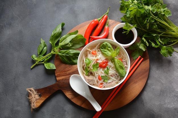 Vietnamese soep pho bo met kruiden, rundvlees, rijstnoedels, chili en taugé.