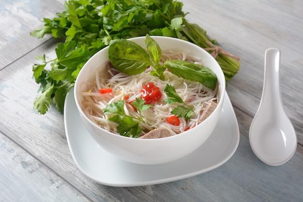 Vietnamese soep pho bo met kruiden, rundvlees, rijstnoedels, chili en taugé