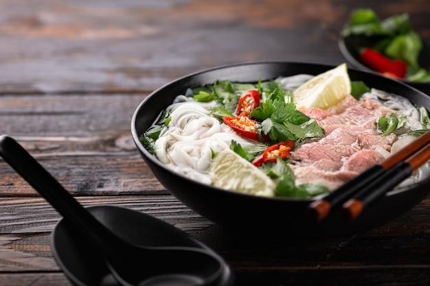Vietnamese soep pho bo met rundvlees en noedels op een houten achtergrond, selectieve aandacht