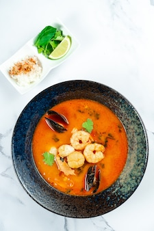 Vietnamese tom yum-soep met zeevruchten. rode soep met garnalen, sint-jakobsschelp, mosselen, zalm in een donkere stijlvolle kom op een marmeren tafel.