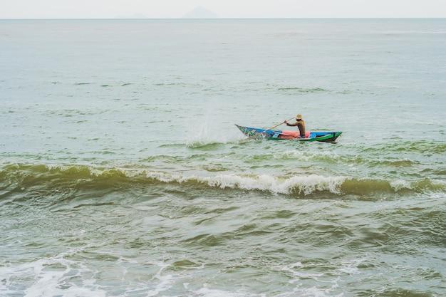 Vietnamese visser zwemt in een boot over de woeste zee.