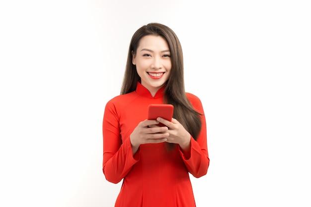 Vietnamese vrouw in traditionele kleding die staat en mobiele telefoon gebruikt die over wit wordt geïsoleerd