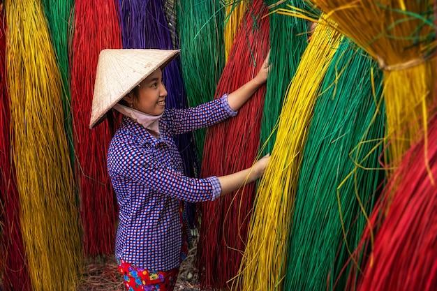 Vietnamese vrouwelijke vakman die traditionele vietnamese matten droogt in het oude traditionele dorp