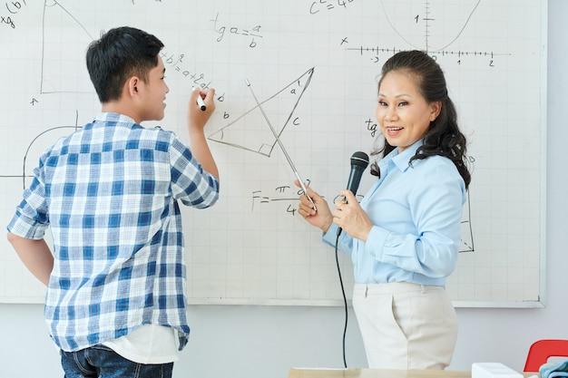 Vietnamese wiskundeleraar die in microfoon spreekt en nieuw onderwerp uitlegt wanneer student vergelijking op whiteboard schrijft