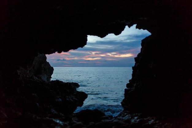 Viev van balinesse-grot bij oceaanstrand op donkerblauwe hemel.