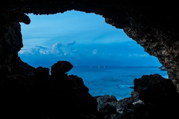 Viev van balinesse-grot bij oceaanstrand op donkerblauwe hemel