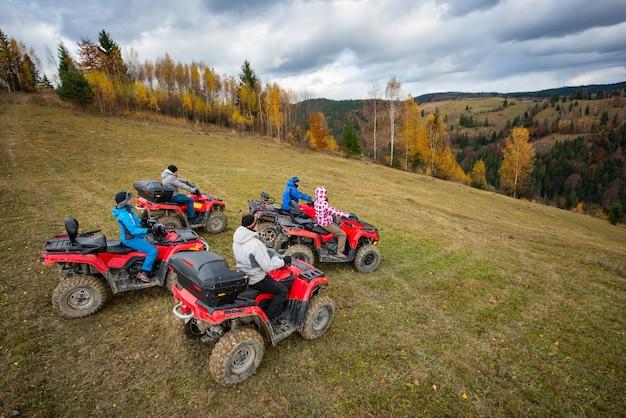 Vijf atv-rijders op off-road quads op de heuvel