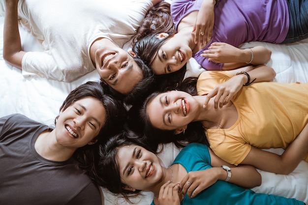 Vijf aziatische jonge vriend die samen plezier hebben in de slaapkamer die van bovenaf is ontsproten terwijl ze samen met het hoofd op het bed liggen