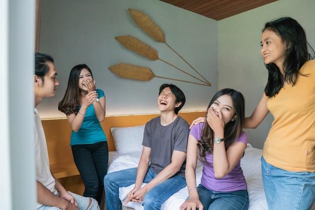 Vijf aziatische jonge vriend met plezier samen in de slaapkamer
