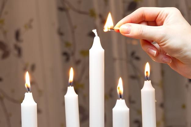 Vijf brandende kaarsen. vrouw hand licht kaarsen romantische sfeer. leuke decoratie.