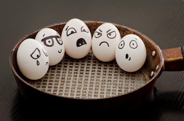 Vijf eieren met geschilderde emoties in een koekenpan, een voedsel-concept