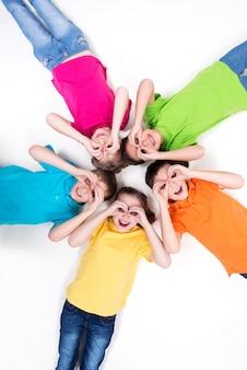 Vijf gelukkige kinderen die op de vloer liggen in een cirkel met handen in de buurt van ogen in heldere t-shirts. bovenaanzicht. geïsoleerd op wit.