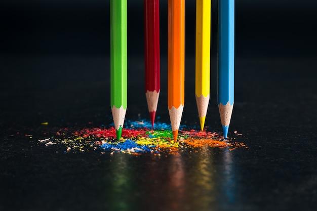Vijf geslepen kleurpotloden in de primaire kleuren van het spectrum staan rechtop tegen een donkere achtergrond in veelkleurige krullen van potloodstiftjes