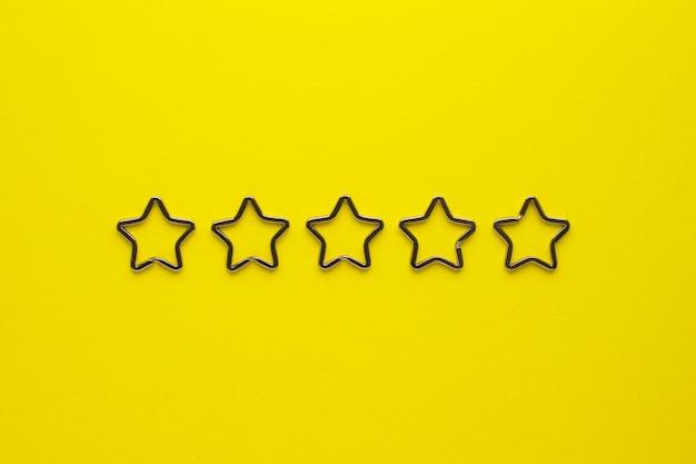 Vijf glanzende metalen split-sleutelhangers in de vorm van een ster voor sleutelhangers. verchroomde sleutelhangersluiting op gele achtergrond.