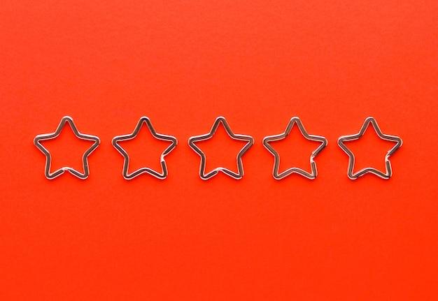 Vijf glanzende metalen split-sleutelhangers in de vorm van een ster voor sleutelhangers. verchroomde sleutelhangersluiting op rode achtergrond. feedback